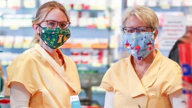 Die Apothekerinnen Anett Spillner (r), und ihre Tochter Julia tragen selbst genähtem Mundschutz. Um das 30-köpfige Team der Apotheke vor einer Ansteckung mit demCoronavirus zu schützen, hat die Chefin früh reagiert. (Foto: dpa)