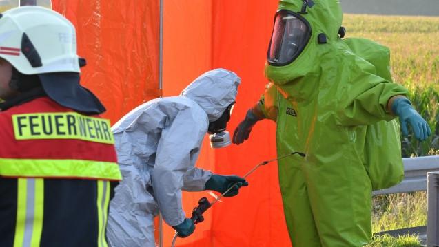 Feuerwehrleute in Schutzanzügen werden nach dem Einsatz an einem  leckgeschlagenen Lkw, der mit 11.000 Liter Salpetersäure beladen ist,  dekontaminiert. (Foto: dpa)