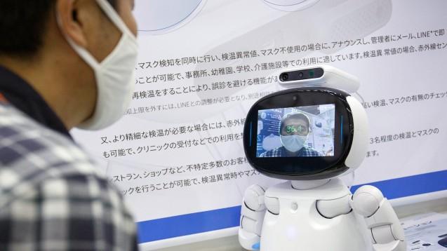 """Ein Besucher der Japan IT Week 2020 überprüft seine Temperatur mit der Wärmebildkamera NUWA Ocular des KI-Roboters """"Kebbi"""". (Foto: IMAGO / ZUMA Wire)"""