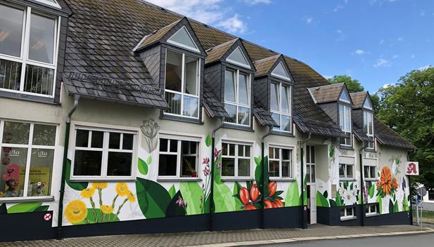 """Die Apothekenfassade nach der Sprühaktion der Graffitikünstler von """"Stark in Form"""": Heilpflanzen und grüne Blätter fallen dem Betrachter sofort ins Auge."""
