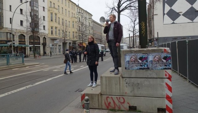 Vor dem BMG stoppte die Gruppe. Die Mitinitiatoren Maximilian Wilke und Maria Zoschke sprachen zu den Teilnehmern und motivierten sie zu einem Pfeifkonzert.