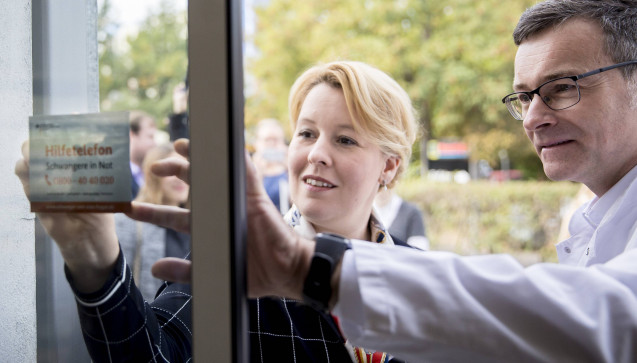 """Bundesfamilienministerin Franziska Giffey (SPD) bringt in der Berliner Pfauen-Apotheke am Eingang einen Aufkleber des Hilfetelefons """"Schwangere in Not"""" an. (Foto: photothek / imago)"""