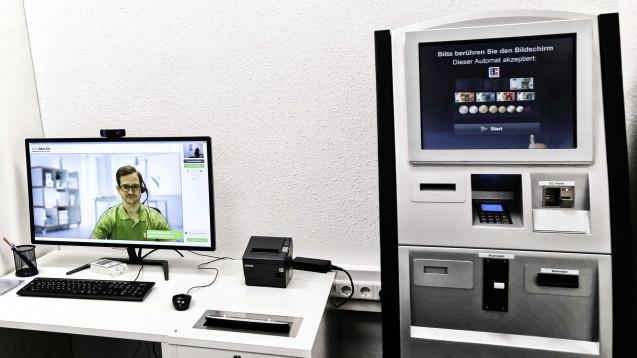 So funktionert der DocMorris-Arzneimittel-Abgabeautomat: Am Schreibtisch kann sich der Kunde via Video-Schaltung pharmazeutisch beraten lassen, links daneben erfolgt die Medikamentenausgabe über den Automaten. Rechts neben dem Schreibtisch ist das Bezahl-Terminal aufgebaut. (Foto: diz)