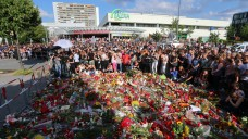 Blumenmeer und stilles Gedenken an die Toten: Trauernde treffen sich am Sonntag beim Olympia-Einkaufszentrum in München. (Foto: dpa)
