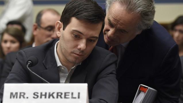 Es geht um umstrittene Medikamentengeschäfte: Shkreli spricht sich bei der Ausschusssitzung im US-Kongress mit seinem Anwalt Benjamin Brafman ab. (Foto: picture alliance / AP Photo)