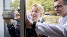 """Bundesfamilienministerin Franziska Giffey (SPD) bringt in der Berliner Pfauen-Apotheke am Eingang einen Aufkleber des Hilfetelefons """"Schwangere in Not"""" an. (c / Foto: photothek / imago)"""