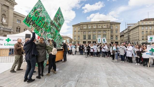 Symbolisch warfen Schweizer Apotheker bei einer Protestaktion das grüne Apotheken-Kreuz in eine große Mülltonne. (Foto: Pharmasuisse)