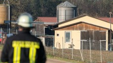 Ein Feuerwehrmann steht am 7.12.2015 vor dem Geflügelhof in Roding (Bayern). Auf dem Hof haben Experten Hinweise auf Geflügelpest gefunden. Knapp 13 000 Tiere mussten notgeschlachtet werden. Foto: Armin Weigel/dpa