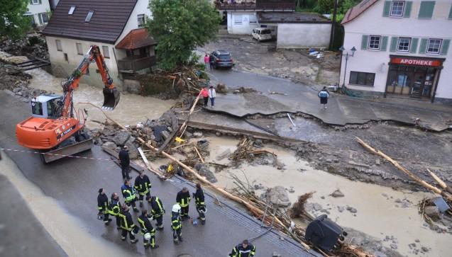 Ein Bagger räumt am 30.05.2016 in Braunsbach die mit Schutt bedeckte und teilweise eingestürzte Straße vor der Apotheke. (Foto: dpa / picture alliance)