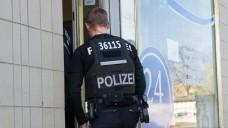 Ein Polizist betritt am Donnerstag ein Büro einer Pflegefirma in Berlin. Mit einem Großaufgebot von Beamten ist die Berliner Polizei gegen organisierten Betrug bei Pflegeabrechnungen vorgegangen. (Foto: Paul Zinken/dpa)
