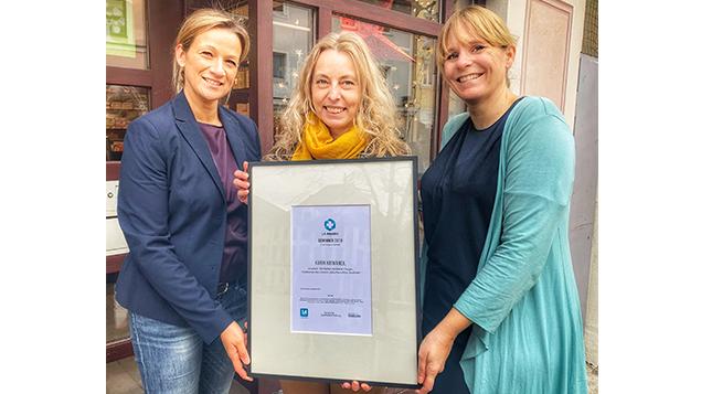 Stefanie Heinz (links), Leiterin Marketing bei 1 A Pharma, und Julia Borsch (rechts), Chefredakteurin DAZonline, überreichen Karin Kriwanek die Urkunde zum Gewinn des diesjährigen 1 A-Awards