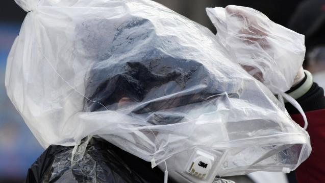 In China greifen die Menschen mittlerweile offenbar zu ungewöhnlichen Mitteln: Hier soll eine Fußgängerin zu sehen sein, die am 11. Februar 2020 im Hauptbahnhof von Peking eine Plastiktüte trägt. ( r / Foto: imago images / Kyodo News)