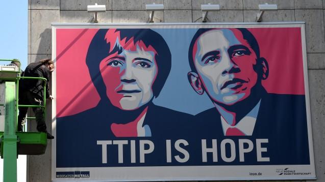 Sind sie weiterhin guten Mutes? Mit einem großflächigen Plakat wirbt der Verband NiedersachsenMetall in Hannover für das Abkommen - während auch Apotheker am Wochenende gegen TTIP protestierten. (Foto: Holger Hollemann / dpa)