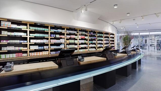 Schwarze Corian-Elemente schaffen einen stimmigen Kontrast zu den Holz- und Glaselementen in der Offizin.