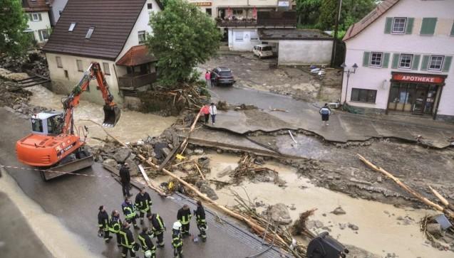 Ein Bagger räumt am 30. Mai 2016 in Braunsbach im Landkreis Schwäbisch Hall in Baden-Württemberg die mit Schutt bedeckte und teilweise zerstörte Straße vor der Apotheke frei. (Foto: picture alliance / dpa)