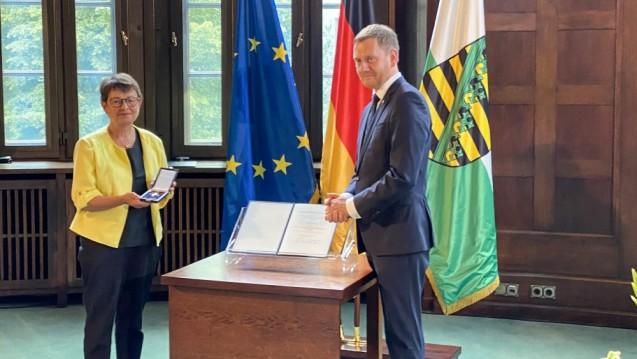 Das Verdienstkreuz am Bande für Monika Koch – überreicht durch den sächsischen Ministerpräsidenten Michael Kretschmer. (x / Foto: SAV)