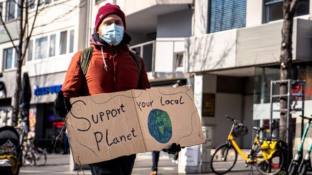 """""""Unterstütze deinen Planeten vor Ort"""", fordert ein Klimaaktivist in Bonn. Auch Apotheker:innen treten vermehrt in Aktion. Auf dem Deutschen Apothekertag 2021 beschäftigen sich zwei Anträge mit der Klimakrise und der Rolle der Pharmazie. (Foto: c / Mika Baumeister / Unsplash)"""