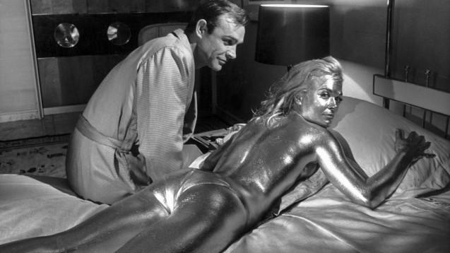 """Sean Connery als James Bond und die goldüberzogene Shirley Eaton als Jill: aufgenommen während der Dreharbeiten zu """"Goldfinger"""" 1964. (p / Foto: picture alliance/KEYSTONE   STR)"""