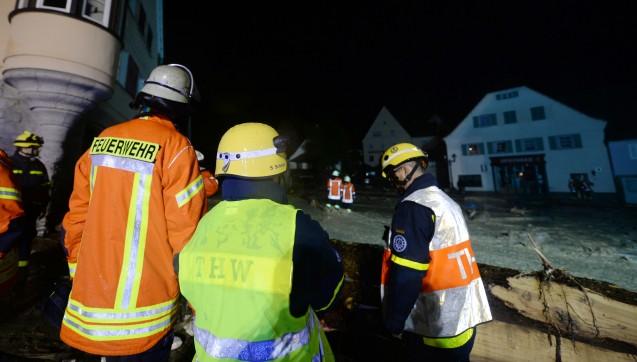 Feuerwehrleute stehen am 30.05.2016 in der Ortsmitte auf einer überfluteten Straße. (Foto: dpa / picture alliance)